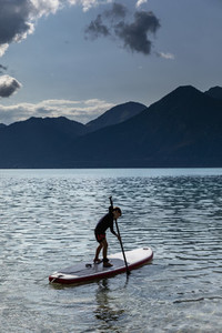 Boy paddleboarding on sunny idyllic lake Walchensee Bavaria Germany