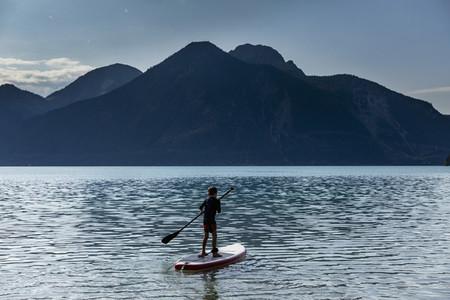 Boy paddleboarding on sunny  idyllic mountain lake  Walchensee  Bavaria  Germany