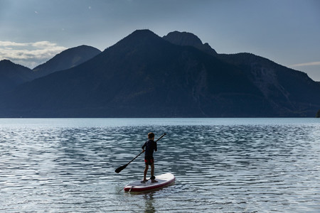 Boy paddleboarding on sunny idyllic mountain lake Walchensee Bavaria Germany
