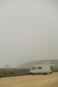 Camper van parked on foggy beach parking lot  Santa Rita Beach  Lisbon  Portugal