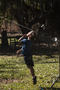 Carefree boy jumping up into sprinkler in sunny back yard
