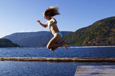Carefree girl jumping off dock into sunny lake  Lake Cowichan  British Columbia  Canada