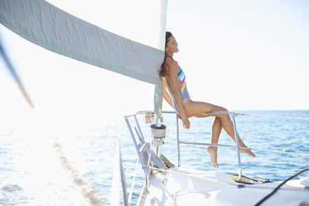 Carefree woman in bathing suit on sunny sailboat