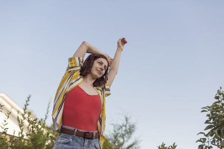 Carefree woman stretching arm overhead