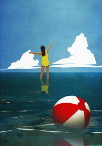 Carefree woman wading in summer ocean behind beach ball