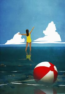Carefree woman wading in summer ocean behind beach ball