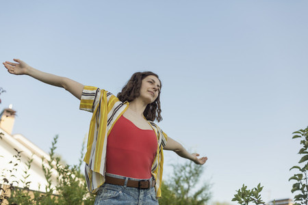 Carefree woman with arms outstretched in back yard