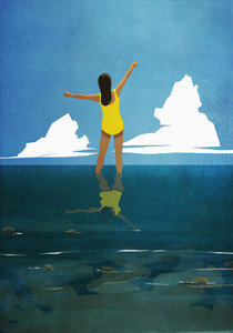 Carefree woman with arms outstretched wading in summer ocean