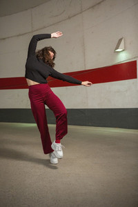 Carefree young woman dancing in tunnel