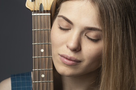 Close up portrait serene young woman with guitar