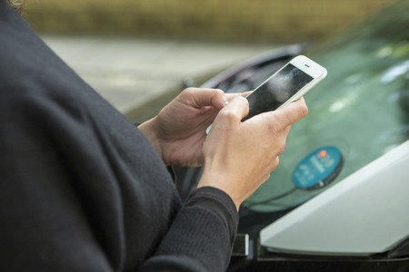 Close up woman using smart phone to access car share