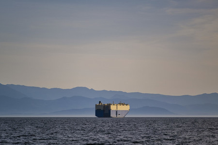 Container ship on sunny idyllic ocean with Olympic Mountain Range in background