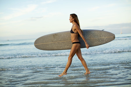 Female surfer carrying surfboard in ocean surf 01