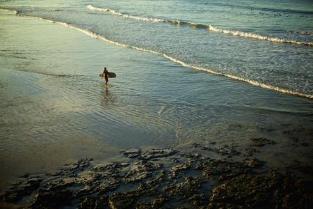 Female surfer carrying surfboard in sunny ocean surf Punta de Mita Nayarit Mexico