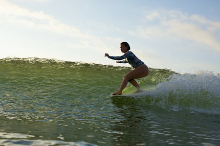 Female surfer riding ocean wave 01