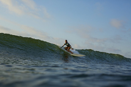 Female surfer riding ocean wave 02