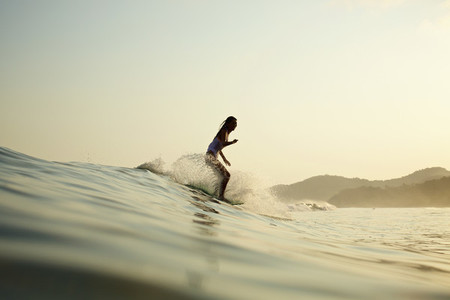 Female surfer riding ocean wave 03
