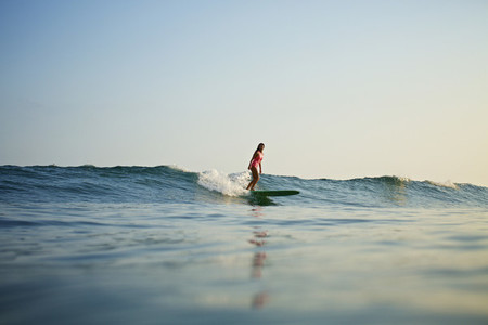 Female surfer riding ocean wave 04