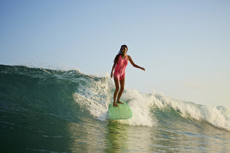 Female surfer riding ocean wave 05