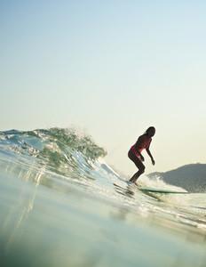 Female surfer riding ocean wave 06