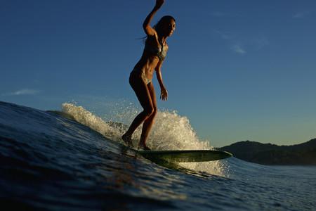 Female surfer riding ocean wave 07