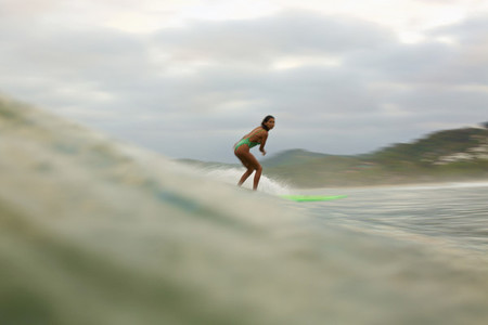 Female surfer riding ocean wave 08