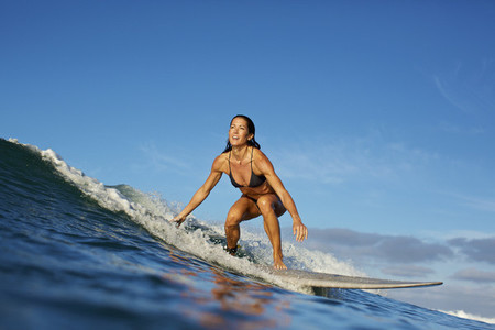 Female surfer riding ocean wave 09