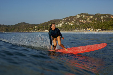 Female surfer riding ocean wave Sayulita Nayarit Mexico