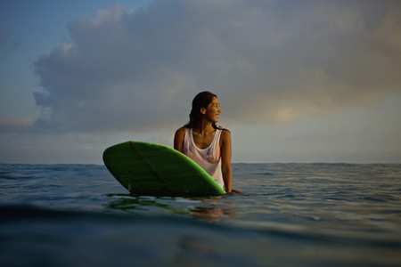 Female surfer waiting on surfboard in ocean 01