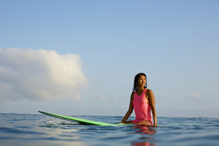 Female surfer waiting on surfboard in ocean 02