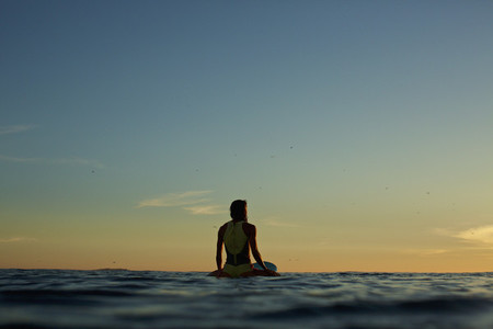 Female surfer waiting on surfboard on ocean at sunset