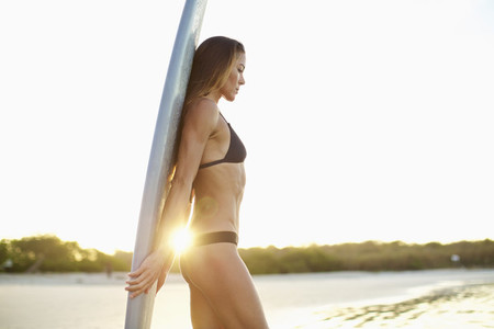 Female surfer with surfboard on sunny beach