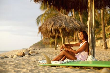 Female surfer with surfboard relaxing on sunny beach