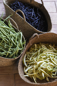 Fresh harvested variety of yellow green and purple beans in straw baskets