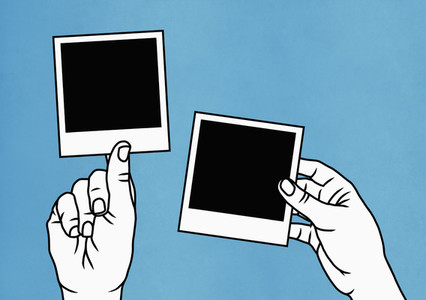 Hands holding instant photographs
