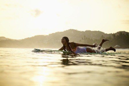 Happy female surfer paddling out in ocean on surfboard Sayulita Nayarit Mexico
