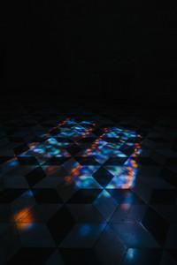 Kaleidoscope reflection of lights on tile floor