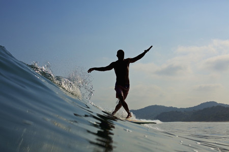 Male surfer balancing on surfboard  riding ocean wave