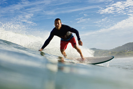 Male surfer riding ocean wave 02