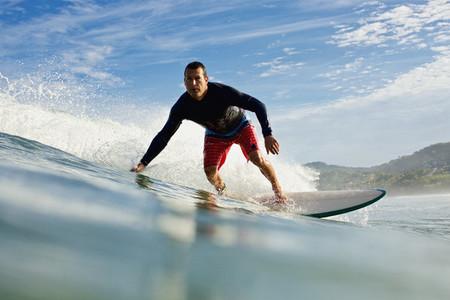 Male surfer riding ocean wave 02