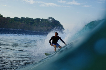 Male surfer riding ocean wave 09