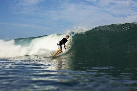 Male surfer riding ocean wave 10