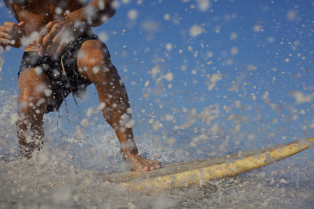 Male surfer riding ocean wave splashing