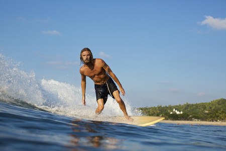 Male surfer riding sunny ocean wave 02