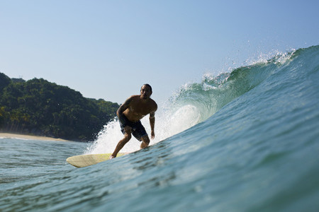 Male surfer riding sunny ocean wave 03