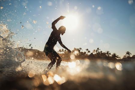 Male surfer riding wave on sunny summer ocean Sayulita Nayarit Mexico