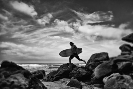 Male surfer with surfboard on rocky ocean beach  Higuera Blanca  Nayarit  Mexico