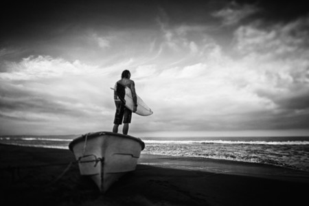 Male surfer with surfboard standing on beached boat Higuera Blanca Nayarit Mexico