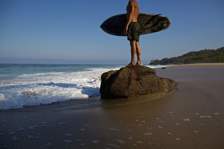 Male surfer with surfboard standing on large stone on beach Sayulita Nayarit Mexico