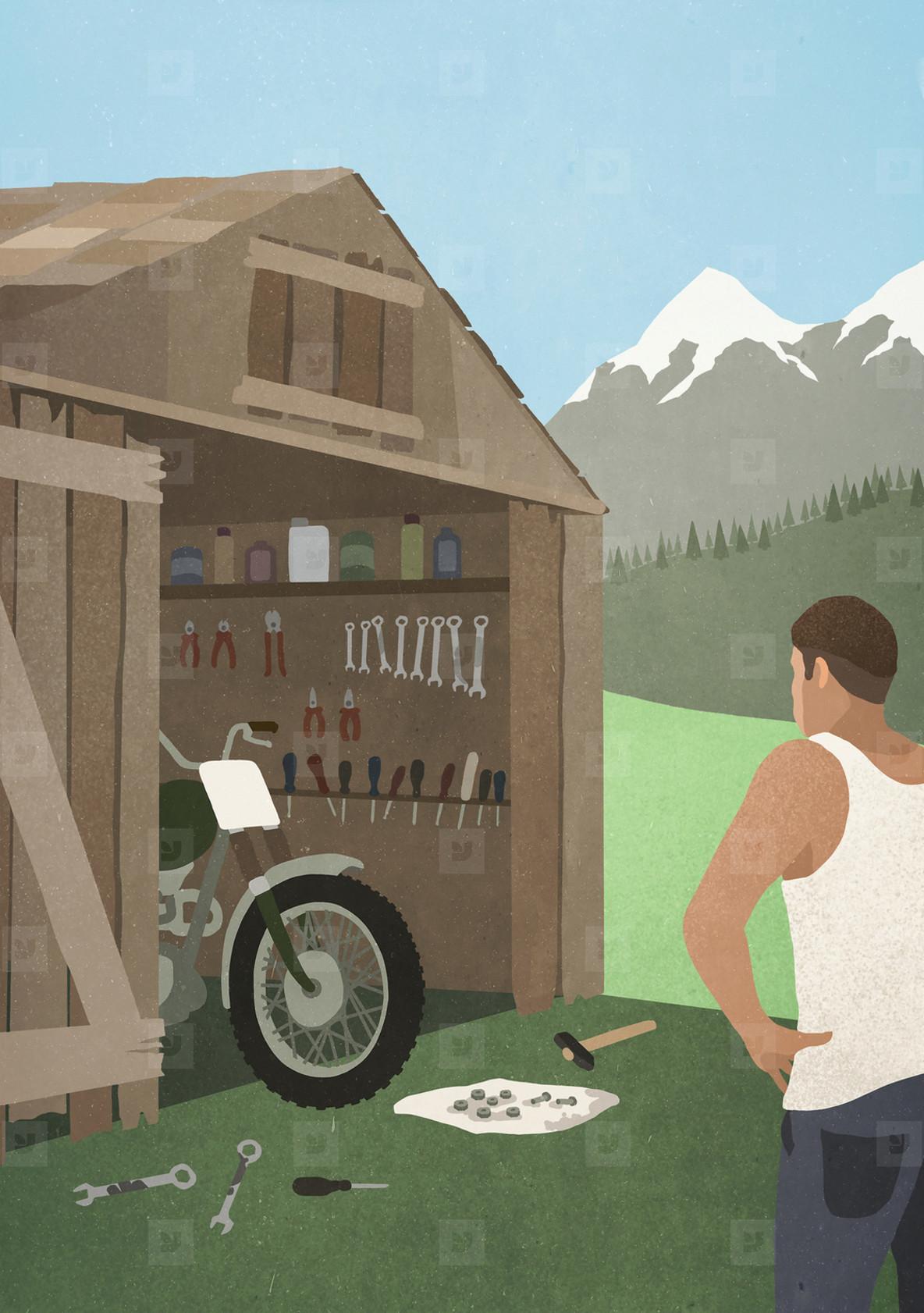 Man standing at garage shed  fixing motorcycle
